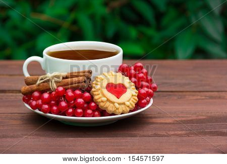 Fragrant tea with cinnamon, cranberry, and homemade cookies. Cookies with jelly in the shape of a heart. Romantic concept. A cup of hot tea with cookies and red berries.