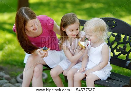 Two adorable little sisters and their mother sharing delicious cream tart outdoors on a beautiful and warm summer day