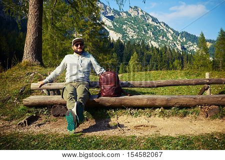 Mid shot of the bearded man sitting on the bench after mountainous walk. Wearing casual comfortable clothes, with a leather brown rucksack, which is lying on the bench.
