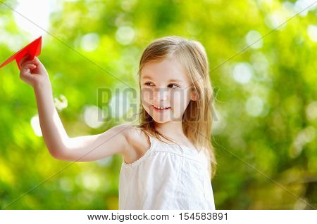 Adorable Little Girl Holding A Paper Plane