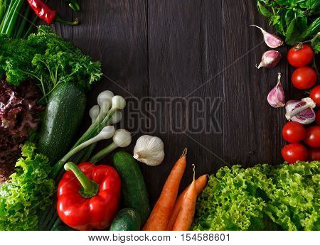 Border of fresh organic vegetables and greens on wood background. Healthy natural food on rustic wooden table with copy space. Italian cuisine cooking ingredients top view,