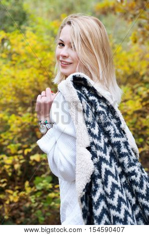 Cute smiling blond woman in black and white knitted warm cardigan strolling in autumn park