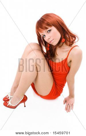 young red hair woman in red dress sitting, studio on white