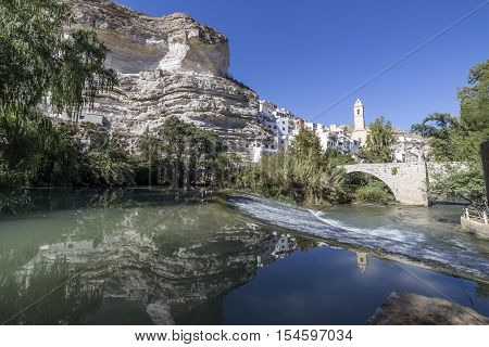 Alcala del Jucar Spain - October 29 2016: Roman bridge located in the central part of the town to its passage by the river Jucar Church of San Andres styles late Gothic and Neoclassic take in Alcala of the Jucar Albacete province Spain