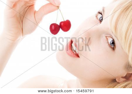 blond woman holding cherryes, close up, looking at camera, studio on white