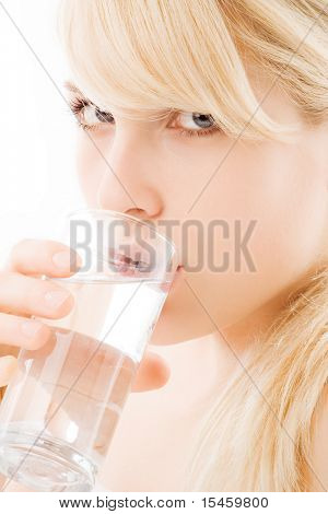 blond young woman drinking a glass of water, close up, studio portrait on white