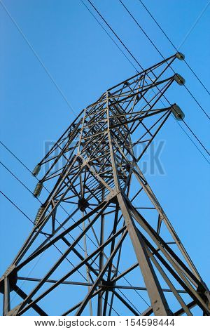 High voltage 110kV reliance power line tower side-bottom view on blue sky