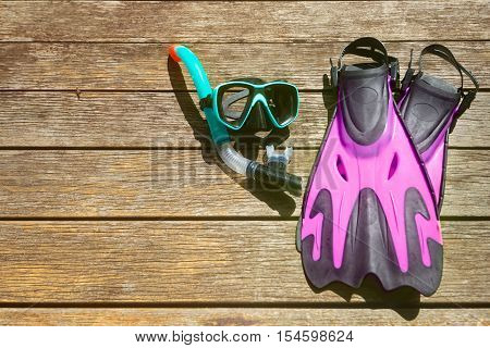Scuba diving and snorkelling. Flippers mask snorkel on wood brown background