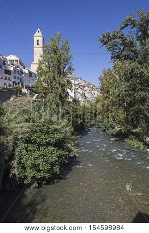 Alcala del Jucar Spain - October 29 2016: Clear waters of the river Jucar on the Roman bridge to the left the Church of San Andres of styles late and neoclassic Gothic take in Alcala of the Jucar Albacete province Spain