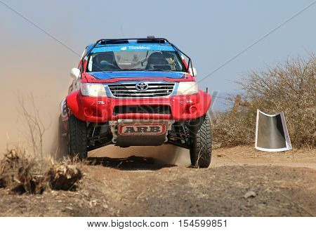 Front View Close-up Of Red And Blue Toyota Hilux Single Cab Rally Car At Road Crossing