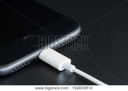 Bangkok Thailand - November 2 2016: Close-up iPhone 7 matte black connect to usb cable new iPhone 7 is manufactured by apple inc.