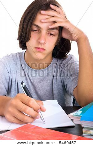 school boy sitting and writing in notebook