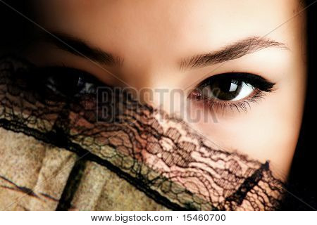 female eyes behind fan