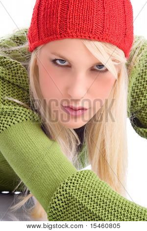 blond young woman in sweater and cap, studio shot