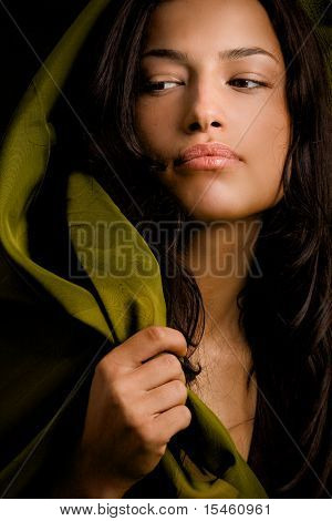 young black hair woman portrait on dark background and with green scarf