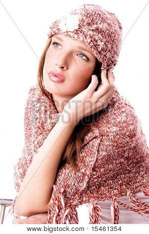 young woman in sweater and red wool cap, studio shot on white