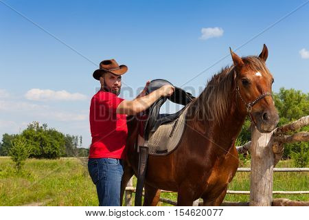 Man in cowboy hat saddling his beautiful horse standing next to the enclosure fence