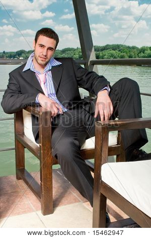 young man in suit, near the river