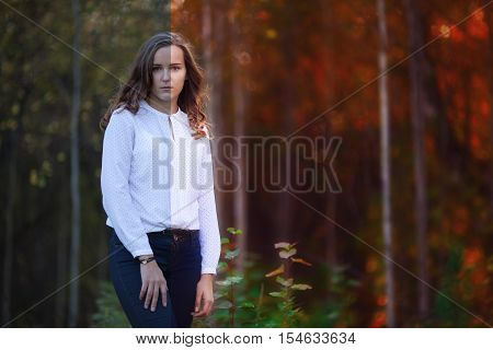 Photo before and after the image editing process. Young beautiful woman in the autumn forest