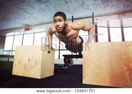 Healthy fitness man doing push-ups in the gym using sports equipment
