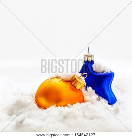 Christmas decoration. Gold ball and blue star on abstract snow background