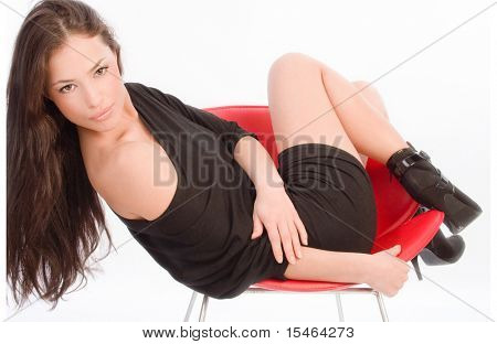 beautiful long hair woman in a red chair, studio white
