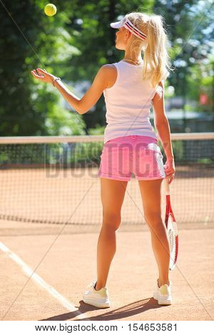 Slim woman prepares for serving on tennis playground outdoor, back view