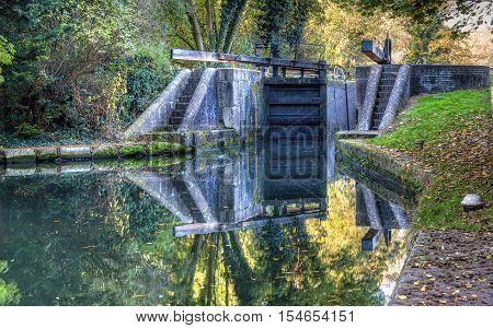 British autumn landscape. Old lock on the canal. HDR style image.