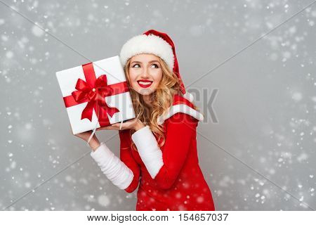 Smiling excited woman in red santa claus outfit holding christmas gift at her ear isolated on the gray background