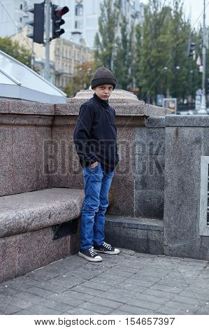 dramatic portrait of a little homeless boy on the street poverty city