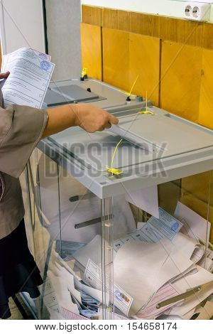 Orel, Russia - September 18, 2016: Woman puts the ballot in the ballot box at polling stations on the day of elections to the State Duma