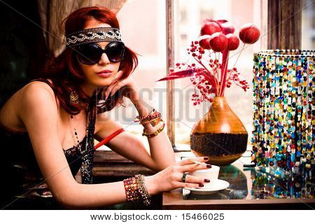 young woman in summer clothes and sunglasses drinking coffee in a restaurant