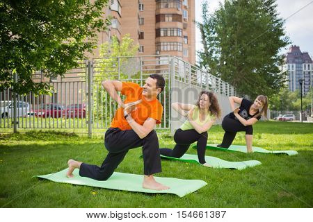Man and two women practice yoga on grass near buildings at summer day