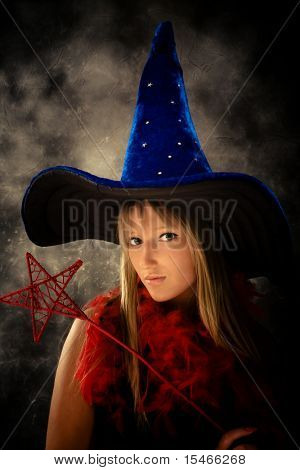 blond teenage girl with wizard hat and wand, studio shot