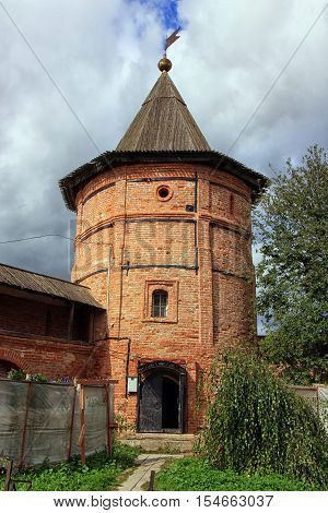 beautiful old medieval circular tower of red brick with gabled wooden roofs