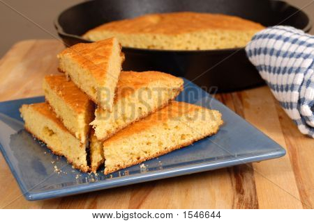 Stack Of Cornbread On A Blue Plate With Skillet In Background