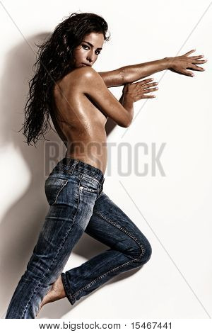 attractive brunette in blue jeans against white wall
