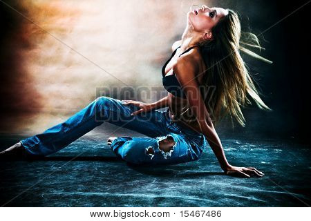 young sexy woman in blue jeans and  brassiere dancing on the floor, studio shot