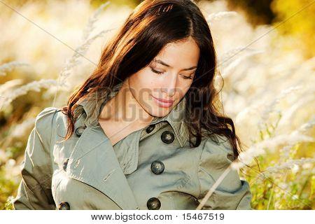 junge Frau im Decklack zu Fuß Accros der Herbst Wiese, sonnigen Herbsttag