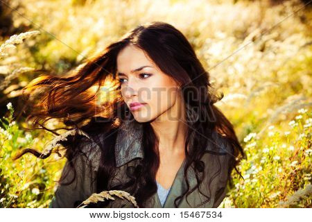 young woman portrait in autumn field, wind in hair