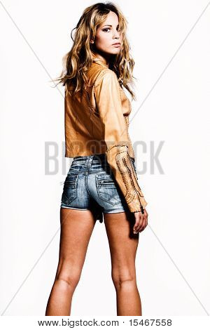 young woman in jeans shorts and leather jacket, stdio shot, white background