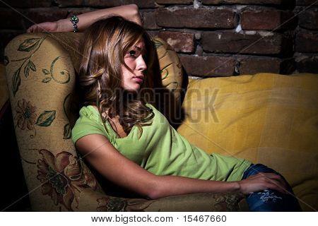 young woman  sit in armchair feeling depressed, indoor shot