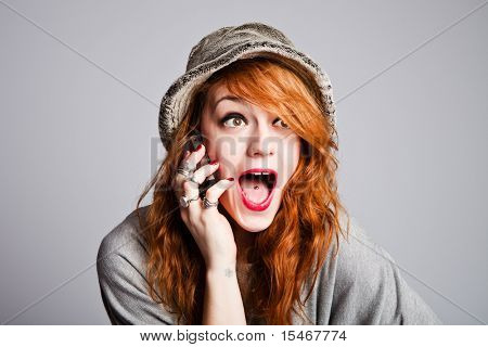 teen woman talking on cellphone, making happy surprice face, studio shot