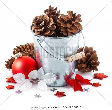 Christmas decoration red balls pinecone in bucket with snowflake and bow. Isolated white background