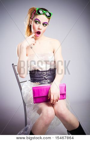 young woman in plastic dress and heavy make up and wonderment expression studio shot