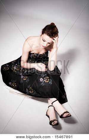 young sad woman in elegant dress sit on floor, studio shot