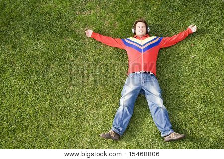 a young man lay down on the grass enjoying good music (with lots of copy space)