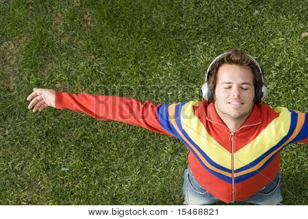 a young man lay down on the grass enjoying good music