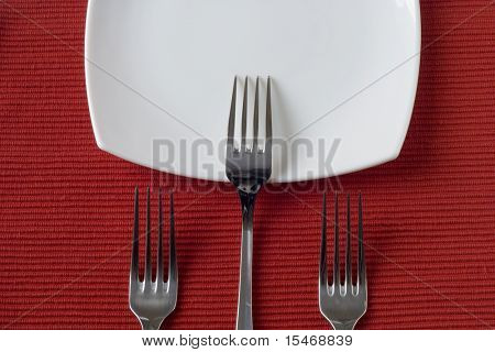 three forks and porcelain plates in a perspective over red (selective and soft focus)