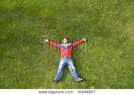 a young man lay down on the grass enjoying good music (lots of copy space)